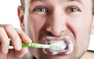 A man cleans his teeth with a manual toothbrush and toothpaste