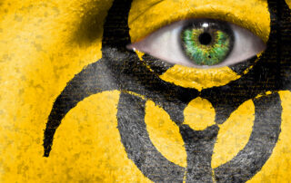 \Face covered with yellow paint and a black hazard symbol stares back at the viewer.