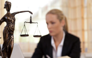 A figure of Justice with her scales in the foreground while a woman sits writing in the background.