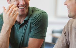 Two men sit talking together. They are both smiling and relaxed.