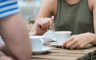A man and a woman sit having a cup of coffee together at a table.