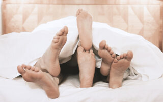Three pairs of feet extend from under a blanket