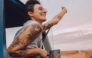 Young woman leans out of a car window with a big smile on her face