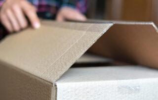 Person unpacks a cardboard box.