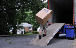 Furniture moving van on a street. Removalist struggles with large box up a ramp into the van.