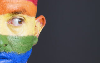 Man with rainbow stripes across his face, looks to the right.