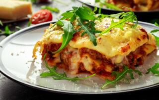 A close up photograph of a serving of lasagna.